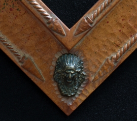 Bronze Indian Mirror Frame Detail Hand carved 5 inch wide x 2 inch tall, wood tone finish with bronze Indian heads in corners, Arrow head accents