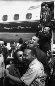 Selma to Montgomery March 1965 Day 4, At the Montgomery Municipal Airport, where a plane load of celebrities arrives. Mrs. King, having greeted Harry Belafonte with an enthousiastic kiss, playfully shares one with Dr. King.