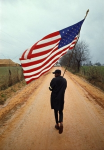 """Selma to Montgomery March 1965 Day 4, Will Henry """"Do-Right"""" Rogers with his hand-made flag and home-made pole, on the Rogert Gardner Farm Road, Lowndes County, 23 March 1965. Call for pricing."""